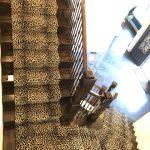 Striking leopard print stair runner over dark hardwood staircase | Bon Air, VA